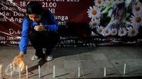 Seorang warga menyalakan lilin saat aksi simpatik dan doa bersama untuk Angeline di Bundaran HI, Jakarta, Kamis (11/6/2015). Mereka meminta pemerintah bersikap tegas kepada pelaku kekerasan anak. (Liputan6.com/Johan Tallo)