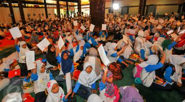 Sebanyak 1.500 anak yatim dan duafa mengikuti kegiatan menulis surat untuk Presiden Jokowi di TMII, Jakarta, Minggu (19/6). Kegiatan tersebut untuk memacu anak berani menuangkan gagasan dan harapannya melalui tulisan tangan. (Liputan6.com/Yoppy Renato)