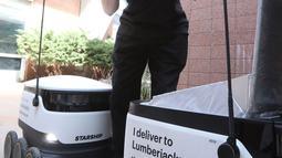 Karyawan rumah makan Michael Sherman menyiapkan makanan untuk diantar oleh robot pengantar makanan di kampus Northern Arizona University, di Flagstaff, Arizona, Amerika Serikat, Selasa (26/3). (Ben Shanahan/Arizona Daily Sun via AP)
