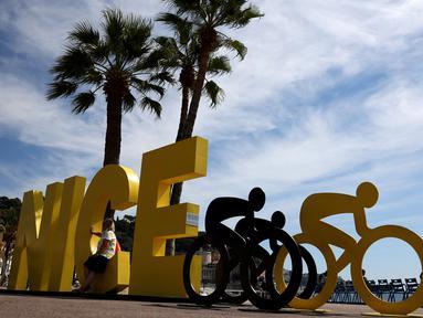 Wisatawan duduk di tulisan Nice dekat ornamen Tour de France2020 di kota Nice, French Riviera, Rabu (26/8/2020). Ajang balap sepeda lintas kota di Prancis ini akan dimulai dari kota Nice pada 29 Agustus hingga 20 September di bawah bayang-bayang 'gelombang kedua' COVID-19. (Kenzo Tribouillard/AFP)