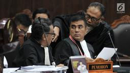 Kuasa hukum Pemohon, Bambang Widjojanto berbincang dengan kuasa hukum Pemohon lainnya saat sidang lanjutan sengketa Pilpres 2019 di Mahkamah Konstitusi, Jakarta, Rabu (19/6/2019). (merdeka.com/Iqbal S. Nugroho)