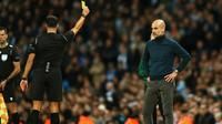 Pelatih Manchester City Pep Guardiola (kanan) mendapat kartu kuning dari wasit saat Manchester City menghadapi Dinamo Zagreb pada laga Liga Champions di Stadion City of Manchester, Inggris, Selasa (1/10/2019). Pep dihadiahi kartu kuning atas protesnya terhadap wasit. (AP Photo/Dave Thompson)