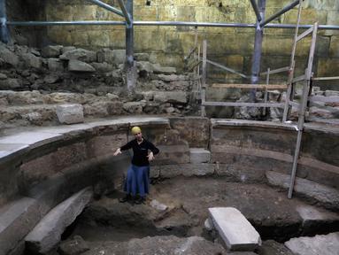 Arkeolog Tehillah Lieberman menunjukkan sebuah teater Romawi kuno yang ditemukan saat penggalian di dekat Tembok Ratapan, sebelah barat Yerusalem, Senin (16/10). Teater itu merupakan bekas era Romawi pertama di Yerusalem. (MENAHEM KAHANA/AFP)