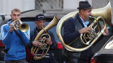 Aksi orkes tiup musisi Rumania untuk mendapat uang di jalanan Warsawa, Polandia pada 21 Oktober 2019. Orkes tiup yaitu sekelompok orang yang memperagakan musik dengan menggunakan instrumen musik tiup baik tiup logam maupun tiup kayu.  (AP Photo/Czarek Sokolowski)