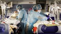 Petugas medis merawat pasien virus corona COVID-19 dalam kereta kecepatan tinggi TGV di Stasiun Gare d'Austerlitz di Paris, Prancis, Rabu (1/4/2020). Prancis mengerahkan kereta kecepatan tinggi untuk mengevakuasi pasien COVID-19 dari Paris ke wilayah Brittany. (Thomas SAMSON/AFP/POOL)