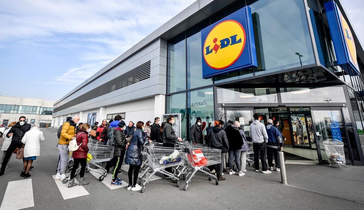 Orang-orang mengenakan masker antre di luar sebuah supermarket di Casalpusterlengo, Minggu (23/2/2020). Mereka memborong perlengkapan dan bahan-bahan kebutuhan pokok karena tak mau keluar rumah menyusul dua warga Italia yang meninggal karena Virus Corona COVID-19. (Claudio Furlan/Lapresse via AP)