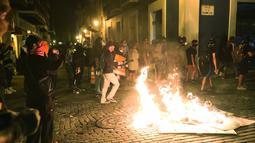 Para pengunjuk rasa membakar sampah saat bentrok dengan polisi di Old San Juan, Puerto Rico (22/7/2019). Para pengunjuk rasa menuntut agar Gubernur Ricardo Rossello mundur  dari jabatannya setelah dalam pusaran skandal pesan teks daring tak senonoh dengan para stafnya. (AFP Photo/Joe Raedle)