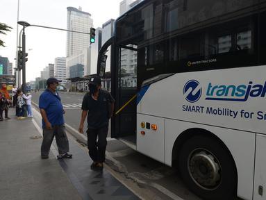 Penumpang turun dari  bus Transjakarta tujuan Kota-Blok M di Halte Pullman, Jakarta,Sabtu (10/10/2020). Moda transportasi umum Transjakarta tetap beroperasi normal, tapi untuk menurunkan penumpang tidak di lajur Bus Transjakarta karena Halte Utama Transjakarta di rusak. (merdeka.com/Imam Buhori)