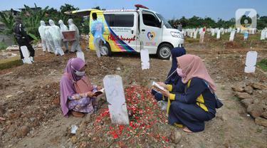 Warga berziarah dengan latar belakang pemakaman korban Covid-19 di TPU Srengseng Sawah 2, Jagakarsa, Jakarta, Senin (17/5/2021). Hari ini seluruh TPU di wilayah DKI dibuka untuk umum dengan menerapkan protokol kesehatan seperti pembatasan pengunjung dan waktu berziarah. (merdeka.com/Arie Basuki)