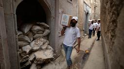 Para relawan Irak di asosiasi lokal saat mendistribusikan jatah makanan ke rumah tangga selama bulan Muslim Ramadhan di kota Mosul utara (7/5/2021). (AFP Photo/Zaid AL-Obeidi)