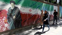 Pejalan kaki melewati lukisan mural yang menggambarkan pendiri Republik Islam Iran Ayatollah Ruhollah Khomeini dan bendera nasional di sepanjang dinding bekas Kedutaan Amerika Serikat (AS) di Ibu Kota Teheran, Iran, Sabtu (22/6/2019). (ATTA KENARE/AFP)