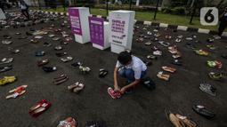"""Pegiat komnas perempuan saat melakukan aksi diam 500 Langkah Awal Sahkan RUU PKS di depan gedung DPR, Jakarta, Rabu (25/11/2020). Dalam aksinya mereka menyusun sepatu sebagai simbol """"semua peduli, semua terlindungi, stop sexual violence"""". (Liputan6.com/Johan Tallo)"""