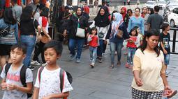 Pejalan kaki melintasi jalur masuk dan keluar Taman Fatahilah saat uji coba simulasi di kawasan Kota Tua, Jakarta, Selasa (23/4). Penataan akses tersebut dilakukan untuk memperlancar keluar masuknya pengunjung ke kawasan wisata tersebut. (Liputan6.com/Immanuel Antonius)