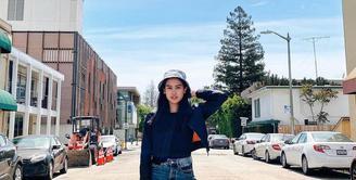OOTD Maudy Ayunda berikut ini bisa kamu tiru untuk hangout. Padukan crop bomber jacket dengan high waist jeans. Sebagai pemanis, kenakan aksesoris berupa bucket hat. (Instagram/maudyayunda).