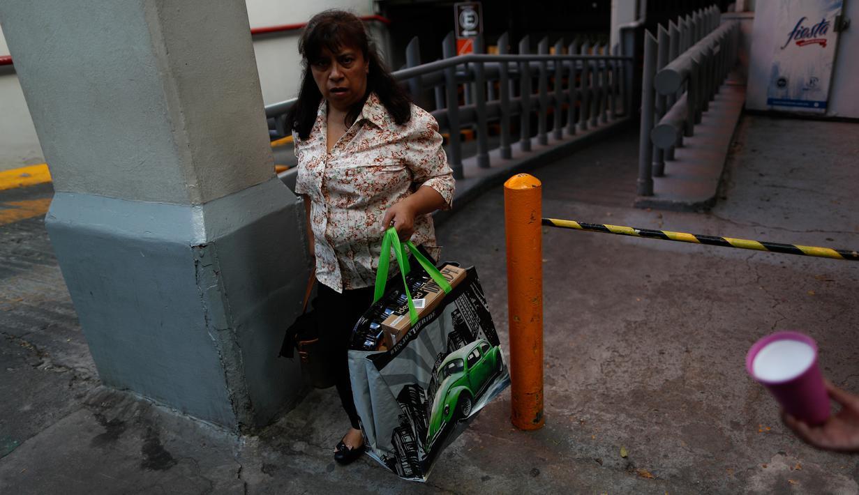 Seorang perempuan membawa tas yang dapat digunakan kembali yang baru dibeli saat meninggalkan toko grosir di Mexico City, 1 Januari 2020. Toko-toko berhenti menyediakan kantong plastik sekali pakai kepada pelanggan sesuai undang-undang yang berlaku di ibu kota Meksiko. (AP/Rebecca Blackwell)