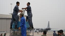 Tim penyemaian awan bersama prajurit Angkatan Udara menyiapkan tangki berisi larutan air garam di Pangkalan Udara Militer Subang, Malaysia, Kamis (19/9/2019). Malaysia melakukan operasi penyemaian awan untuk mendorong hujan dalam mengatasi kabut asap yang melanda. (AP Photo/Vincent Thian)