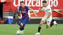 Striker Barcelona, Lionel Messi, berebut bola dengan penyerang Sevilla, Munir El Haddadi, dalam laga lanjutan La Liga Spanyol, Sabtu (20/6/2020) dini hari WIB. Barcelona bermain imbang 0-0 atas Sevilla. (AFP/Cristina Quicler)