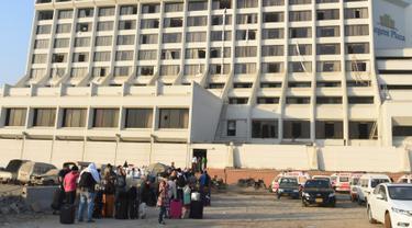 Para tamu berkumpul di luar sebuah hotel mewah yang mengalami kebakaran di kota Karachi, Pakistan, Senin (5/12). Sedikitnya 11 orang tewas dan puluhan lainnya luka-luka akibat musibah tersebut. (RIZWAN Tabassum/AFP)