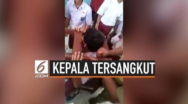 Seorang bocah laki-laki terjebak di sela-sela kursi sekolahnya lantaran kepalanya tersangkut. Beberapa cara dicoba para guru untuk melepaskan kepala bocah tersebut dari kursi. Salah satunya dengan menggergaji kursi.