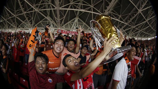 Suporter Persija Jakarta mengangkat replika piala saat merayakan gelar juara Liga 1 di SUGBK, Jakarta, Minggu (09/12). Persija menang 2-1 atas Mitra Kukar. (Bola.com/M Iqbal Ichsan)