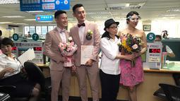Pasangan sesama jenis Shane Lin dan Marc Yuan serta Cynical Chick dan Li Ying-Chien berpose di kantor pemerintahan Taipei, Taiwan, Jumat (24/5/2019). Diperkirakan ada sekitar 300 pasangan sesama jenis lainnya yang mendaftarkan pernikahan mereka pada hari yang sama. (AP Photo/Johnson Lai)