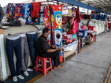 Pedagang menunggu pembeli di Jembatan Penyeberangan Multiguna atau Skybridge Tanah Abang, Jakarta, Jumat (19/6/2020). Kendati pusat perbelanjaan telah dibuka sejak 15 Juli 2020, aktivitas jual beli di Skybridge Tanah Abang terpantau sepi. (Liputan6.com/Faizal Fanani)