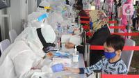 Petugas medis memeriksa seorang anak saat rapid test oleh BIN di Lapangan Kantor Kecamatan Pamulang, Tangerang Selatan, Banten, Kamis (2/7/2020). BIN menggelar rapid test gratis terhadap 800 warga Pamulang untuk memutus mata rantai penyebaran virus corona COVID-19. (merdeka.com/Arie Basuki)