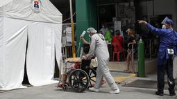 Seorang petugas kesehatan yang mengenakan pakaian pelindung mendorong pasien COVID-19 ke tenda isolasi di luar rumah sakit di Manila, Filipina, Senin (26/4/2021). Infeksi virus corona COVID-19 di Filipina melonjak melewati 1 juta pada hari Senin dalam tonggak suram terbaru. (AP Photo/Aaron Favila)