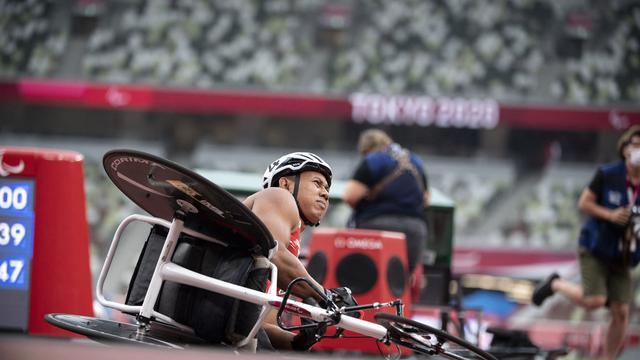 Atlet Indonesia, Jaenal Aripin, sempat terjatuh setelah melewati garis finis di atletik 100 meter putra T54 Paralimpiade Tokyo 2020, Rabu (1/9/2021). (AFP/Charly Triballeau)