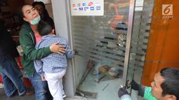 Murid TK, Fathur dipeluk ibunya saat tangannya terjepit kaca pintu ATM Bank BNI di Jalan M. Saidi, pesanggrahan, Jakarta Selatan, Senin (5/8/2019). Fathur terjepit pintu saat ibunya mengambil uang di ATM tersebut. (merdeka.com/Arie Basuki)