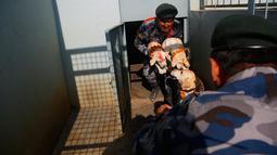 Personel polisi Nepal memegang anak anjing ketika mereka disembah selama festival Tihar di Kathmandu, Selasa (6/11). Selama lima hari perayaan, pemujaan dilakukan pada hewan-hewan berbeda yang erat kaitannya dengan dewa-dewi Hindu. (AP/Niranjan Shrestha)
