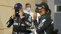 Pembalap Mercedes Lewis Hamilton (kanan), dan pembalap Mercedes Valtteri Bottas memakai masker usai sesi kualifikasi di Formula 1 Sirkuit Internasional Bahrain di Sakhir, Bahrain, Sabtu (28/11/2020). Lewis Hamilton dinyatakan positif COVID-19. (Hamad Mohammed, Pool via AP, File)
