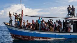 Pengungsi etnis Rohingya berada di atas kapal milik nelayan Indonesia di pesisir Pantai Seunuddon, Aceh Utara (24/6/2020). Sebanyak 94 pengungsi etnis Rohingya yang lelah dan kelaparan, termasuk 30 anak-anak ditemukan terdampar di pesisir Pantai Seunuddon. (AP Photo/Zik Maulana)