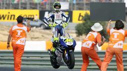 Valentino Rossi berdiri di atas motornya saat merayakan kemenangan dalam MotoGP di Portugal pada September 2007. (AFP/Francisco Leong)