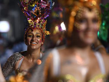 Anggota karnaval Uruguay, Comparsa, melakukan pertunjukkan tari selama parade karnaval Llamadas di Montevideo, Kamis (7/2). Para penari dengan menggunakan berbagai kostum menarik meriahkan parade tersebut di jalanan Montevideo. (PABLO PORCIUNCULA/AFP)