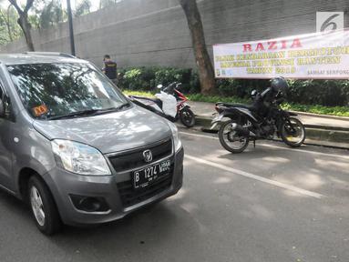 Anggota Satlantas Polres Tangerang Selatan memeriksa kelengkapan surat saat razia pajak kendaraan di Jalan BSD, Tangerang Selatan, Kamis (24/1). Razia ini untuk mendisiplinkan pengendara terhadap pembayaran pajak kendaran. (Merdeka.com/Arie Basuki)