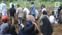 Keluarga menyaksikan pemakaman jenazah korban COVID-19 di TPU Tegal Alur, Jakarta, Kamis (17/12/2020). Hingga hari ini, intensitas pemakamanan korban covid-19 di DKI masih tinggi dengan rata-rata yang dimakamkan mencapai 30 hingga 38 jenazah per hari. (merdeka.com/Arie basuki)