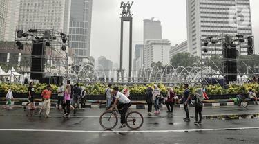 Warga beraktivitas saat car free day (CFD) di kawasan Bundaran HI, Jakarta, Minggu (29/12/2019). Kendati tidak seramai saat cerah, warga yang berlari, jalan santai, atau swafoto masih menjadi pemandangan di area CFD usai hujan mengguyur Jakarta. (Liputan6.com/Faizal Fanani)