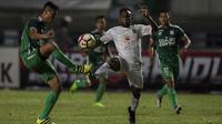 Striker Persebaya, Ricky Kayame, berebut bola dengan bek PSMS, Roni Fatahillah, pada laga final di Stadion GBLA, Bandung, Selasa (28/11/2017). Persebaya menang 3-2 atas PSMS. (Bola.com/Vitalis Yogi Trisna)