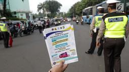 Petugas Dinas Perhubungan menunjukkan selebaran sosialisasi pemberlakuan sistem ganjil genap di pintu masuk Gardu Tol Cibubur 2, Jakarta, Senin (16/4). Aturan ini berlaku untuk kendaraan pribadi atau golongan I dan II. (Liputan6.com/Faizal Fanani)