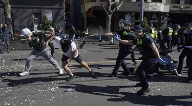 Polisi menggunakan semprotan merica pada pengunjuk rasa selama protes anti-lockdown di Melbourne, Australia, Sabtu (21/8/2021). Para pengunjuk rasa berunjuk rasa menentang pembatasan pemerintah yang ditempatkan dalam upaya mengurangi wabah COVID-19. (James Ross/AAP Image via AP)