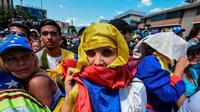 Demonstran mengenakan benedera Venezuela di kepalanya dalam aksi protes mendesak pengunduran diri Nicolas Maduro (AFP/Juan Baretto)