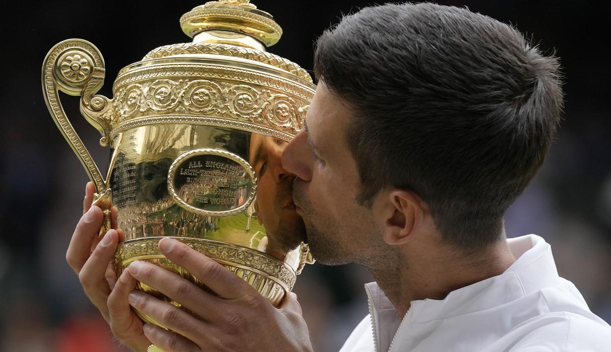 Petenis Serbia, Novak Djokovic cium Piala Wimbledon usai kalahkan petenis Italia, Matteo Berrettini di partai puncak tunggal putra. Kemenangan ini mengantarkan Djokovic menyamai rekor Nadal dan Federer sebagai petenis yang mampu mendapatkan 20 gelar Grand Slam. (Foto: AP/Kirsty Wigglesworth)