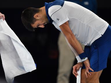 Petenis Serbia, Novak Djokovic tertunduk karena  kehilangan poin saat melawan petenis asal Korea, Hyeon Chung pada ajang Australia Terbuka 2018 di Melbourne,  (22/2/2018). Djokovic kalah 6-7, 5-7, 6-7. (AFP/Paul Crock)