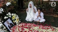 Bunga Citra Lestari atau BCL bersama anaknya Noah Sinclair duduk di samping makam Ashraf Sinclair di San Diego Hills, Karawang, Jawa Barat, Selasa (18/2/2020). Keluarga dan kerabat mengiringi pemakaman jenazah Ashraf Sinclair. (Liputan6.com/Faizal Fanani)