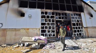 Orang-orang melihat bangsal isolasi corona COVID-19 yang rusak di rumah sakit Al-Hussein setelah kebakaran besar di kota Nasiriyah, Selasa (13/7/2021). Selain dihadapi oleh perang dan sanksi, Irak juga berusaha bertahan dengan sistem medisnya dalam mengatasi krisis Virus Corona. (Asaad NIAZI/AFP)