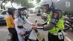 Anggota Satlantas Polres Tangerang Selatan memeriksa kelengkapan surat saat razia pajak kendaraan di Jalan BSD, Tangerang Selatan, Kamis (24/1). Razia juga untuk meningkatkan tertib lalu lintas dan disiplin pengendara bermotor. (Merdeka.com/Arie Basuki)