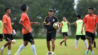 Pelatih Arema FC, Joko Susilo (topi), tengah memimpin latihan. (Bola.com/Iwan Setiawan)