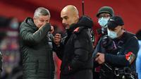 Manajer Manchester United, Ole Gunnar Solskjaer (kiri), berbincang dengan manajer Manchester City, Josep Guardiola usai laga lanjutan Liga Inggris 2020/21 pekan ke-12 di Old Trafford Stadium, Sabtu (12/12/2020). Manchester United bermain imbang 0-0 dengan Manchester City. (AFP/Paul Ellis/Pool)