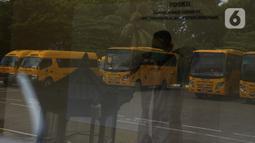 Petugas mengenakan APD sebelum menjemput pasien Covid-19 menggunakan bus sekolah di Puskesmas Jatinegara,  Jakarta, Selasa (22/9/2020). Sejumlah unit bus sekolah kini dialihfungsikan menjadi kendaraan untuk mengantar pasien Covid-19 berstatus OTG menuju Wisma Atlet. (merdeka.com/Imam Buhori)
